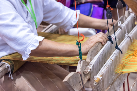 Hands of woman weaving traditional cotton woven.
