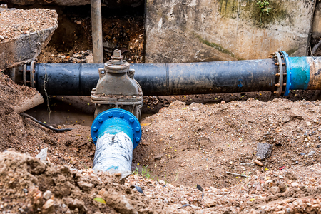 plumber: Water PVC Plastic Pipes in Ground during Plumbing Construction site.