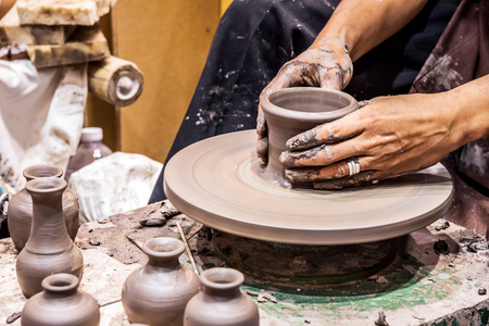 Hands working on pottery wheel, was produced on range of vase, Selective focus.
