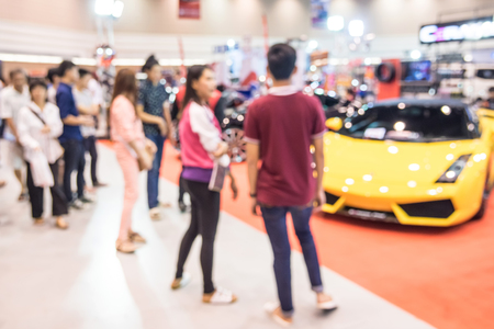 show room: Abstract people walking in motor show, car show room blurred defocusing background. Concept of business social gathering for meeting exchange.