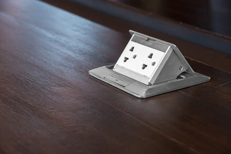 baseboard: Electric outlet on wooden floor. Interior design detail power outlet. Stock Photo