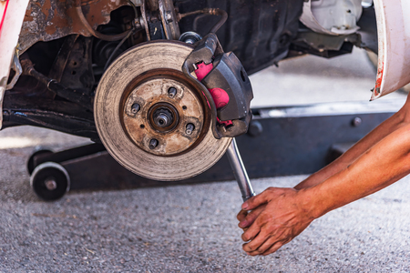 scheduled replacement: Mechanic technician worked replacing brakes vehicle of automobile at repair service station.