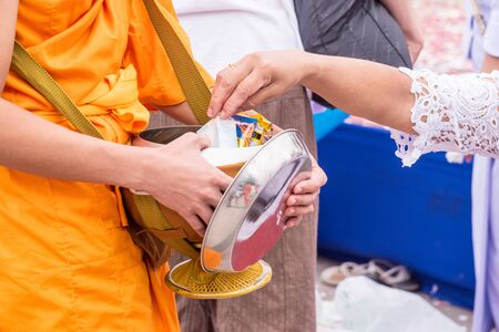 People Gives food offerings to a Buddhist monk. Stock Photo