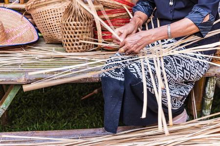 basket weaving: Elderly female hands manually weaving bamboo basket. Stock Photo