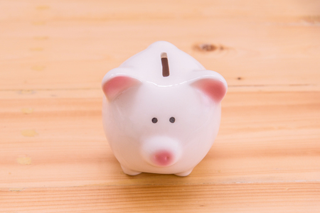 Piggy bank a container for saving money in, on wooden top table, money savings concept