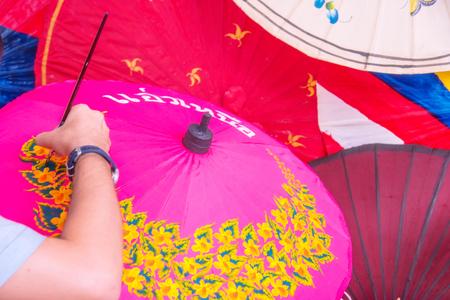 bo: Man painting on Handmade umbrella of the village Bo Sang, Chiang mai, Thailand.