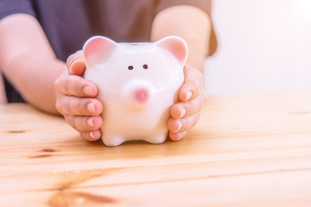 putting money in pocket: Piggy bank in hand on wooden top table, money savings concept