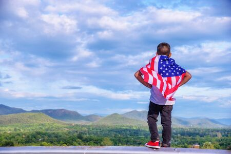 The boy cover body by the American flag celebrating nation day, look ahead mountains.