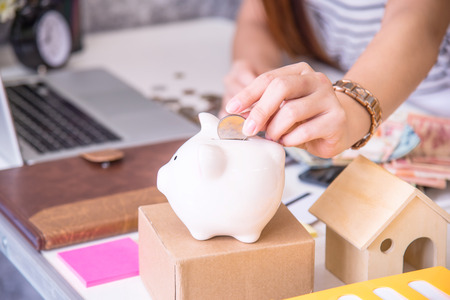 putting money in pocket: Coins on hand are dropped Piggy bank on wooden top table, money savings concept  Stock Photo