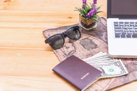 Travel concept,passport, money, map, sunglasses on wooden table.Travelers accessories, Top view with copy space.