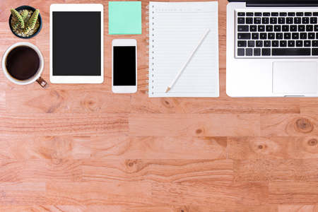 Wooden office desk table with laptop computer, smartphone, notebook and cup of coffee. Top view with copy space, flat lay. Stock Photo