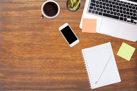 Business working at an office, Modern office desk table with laptop computer, smartphone, and cup of coffee. Top view with copy space, flat lay.