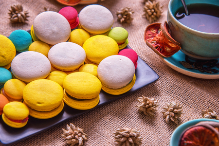 Colorful french macarons with cup of bael tea on table. Macaron is popular dessert for served with tea or coffee Stock Photo
