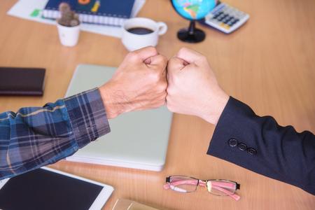Friendship business with hands together, office desktop on background, concept of teamwork.