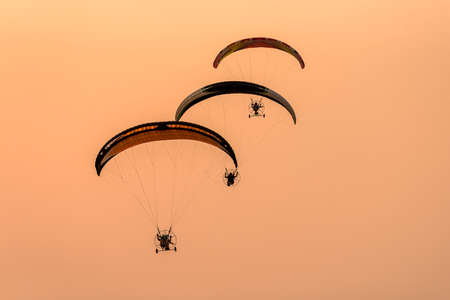 Silhouette of the Paramotor gliding and flying In the air through soft sunlight sky. Paramotor it is extreme sport Imagens