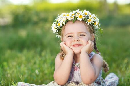 Little girl in nature with a wreath of flowers on her head.