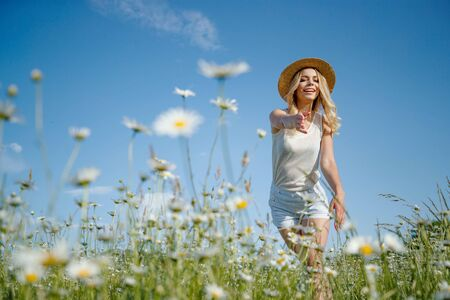 Woman in a field with flowers. Beautiful woman runs across the field with daisies.