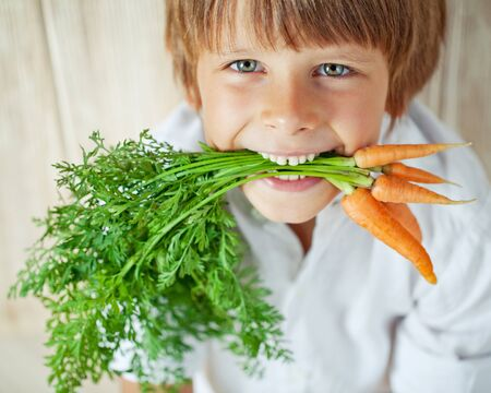 Child boy holding a carrot in his hands. Child and vegetables.