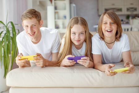 Children teenagers play a game on the phone at home. Foto de archivo