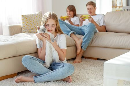 Children play different games. The girl holds a cat in her arms, and the boys play on the phones.