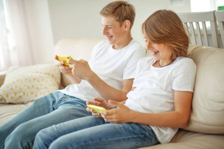 Children teenagers at home have fun. Two friends play on the phones. 版權商用圖片 - 148072408