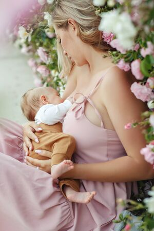 Young woman is breastfeeding a baby on nature. Banco de Imagens