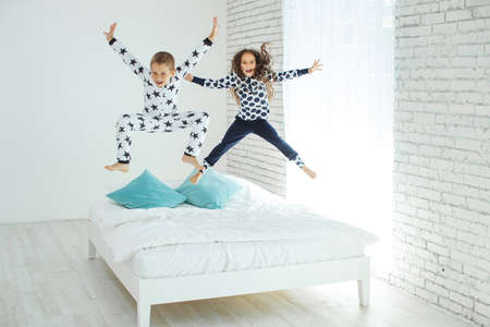 Children jump on the bed.The boy and the girl are having fun. High quality photo. 版權商用圖片