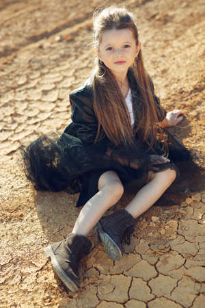 Childrens fashion. Fashionable child. Girl outdoors in fashionable clothes. High quality photo.