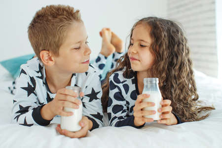 Children drink milk. Boy and girl at home. High quality photo.