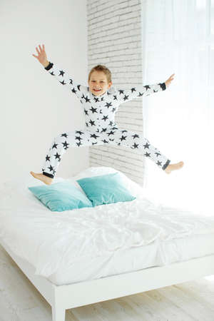 Child on the bed in pajamas. High quality photo.