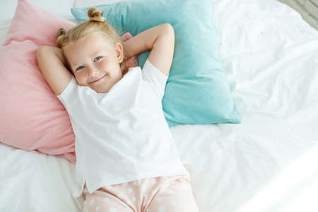 Little girl in bed with white linen. A child at home in the morning wakes up in his room. High quality photo.