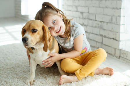 Little girl with a dog at home. High quality photo.