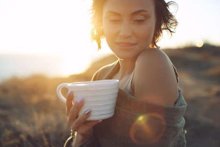 Beautiful woman drinks coffee. Woman outdoors. High quality photo.