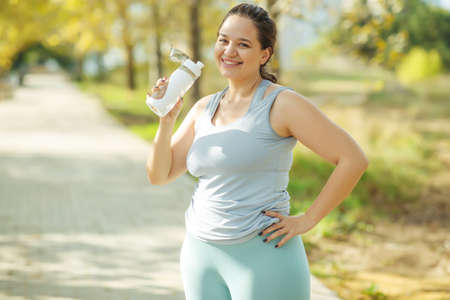 Fat woman and sports. Does exercise for weight loss in the fresh air. High quality photo. Stock Photo