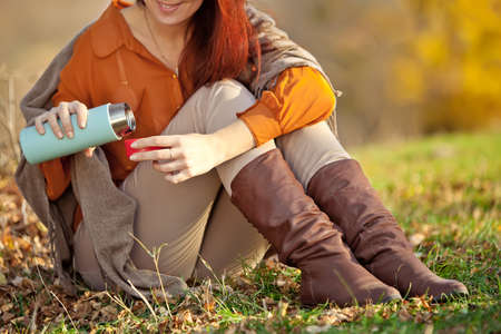 A woman in warm knitted clothes drinks a cup of hot tea or coffee outdoors in the sunlight. High quality photo.