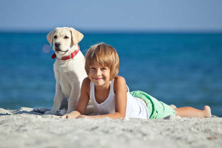 Happy boy playing with his dog on the seashore against the blue sky. Best friends have fun on vacation. High quality photo.