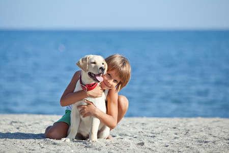 Happy boy playing with his dog on the seashore against the blue sky. Best friends have fun on vacation. High quality photo. Imagens