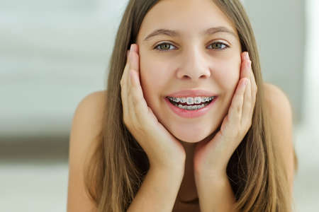 Close up portrait of smiling teenager girl showing dental braces.Isolated on white background. High quality photo. Stock Photo