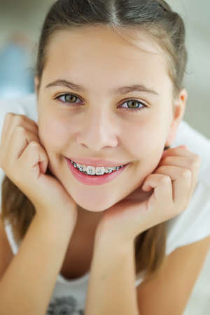 Close up portrait of smiling teenager girl showing dental braces.Isolated on white background. High quality photo.