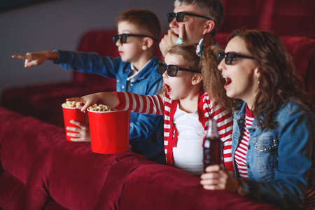 Family mom father and children are watching a projector, TV, cinema, movies with popcorn in the cinema. High quality photo.