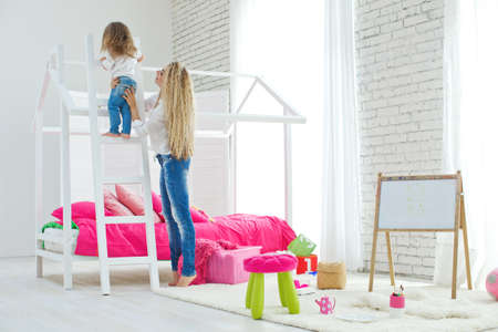 Happy loving family. Mother and daughter in the childrens room. Funny mom and lovely baby having fun indoors. Cute little girl is playing with a woman. High quality photo. Archivio Fotografico