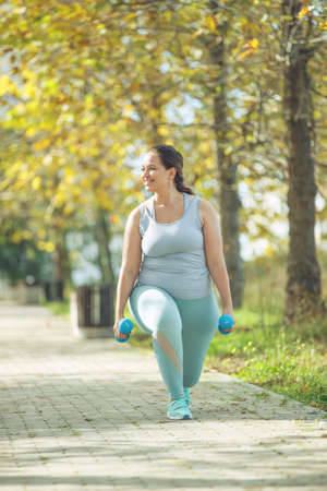 An attractive plus size woman in a sports top and leggings, goes in for sports, works out in a cozy city park. High quality photo. 免版税图像