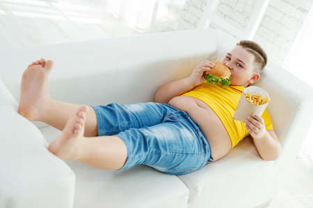 A boy with metabolic disorders. Child with the problem of childhood obesity. Overweight obese fat boy. High quality photo.