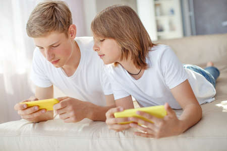 leisure, technology, technology, family and people concept - happy boys and boy with smartphones sending text messages or playing games at home. High quality photo. Stock Photo
