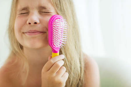 Little girl with long hair and comb in the hands of caring for her hair. High quality photo.