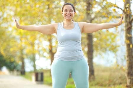 An attractive plus size woman in a sports top and leggings, goes in for sports, works out in a cozy city park. High quality photo.