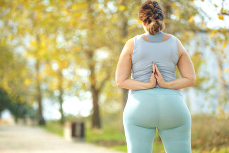 An attractive plus size woman in a sports top and leggings, goes in for sports, works out in a cozy city park. High quality photo. Stock Photo