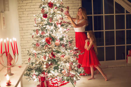 Merry Christmas and Happy Holidays. Mom and daughter with a Christmas tree indoors at night. The evening before Christmas. Portrait of a loving family nearby. High quality photo.