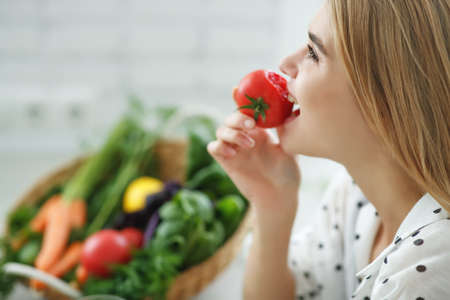 Beautiful young woman eating vegetables in the kitchen. Healthy food. Vegan salad. Diet. Diet concept. Healthy lifestyle. Cook at home. High quality photo.