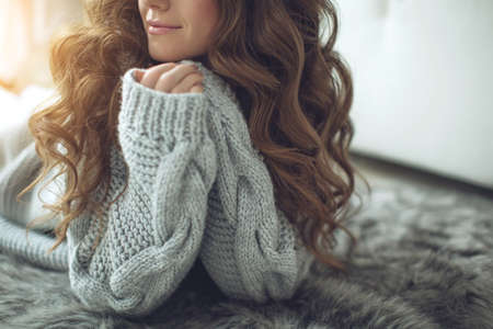 Young beautiful woman in warm knitted clothes at home. Female indoor portrait. High quality photo. Stockfoto